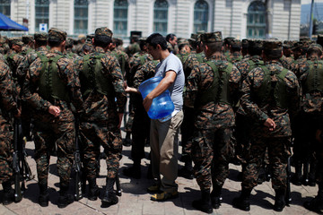 A man sells water to Salvadoran reserve army soldiers after an official ceremony prior to their deployment to deal with gang violence in San Salvador