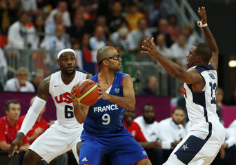 France's Parker is guarded by James and Paul of the U.S. during their men's Group A basketball match at the London 2012 Olympic Games in the Basketball arena