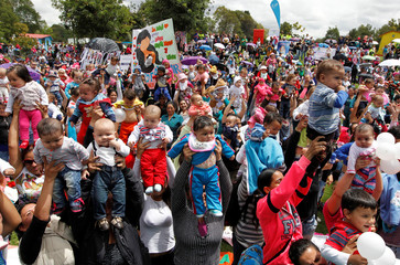 Mothers hold up their babies, as part of the celebration for World Breastfeeding Week, at Lovers Park in Bogota