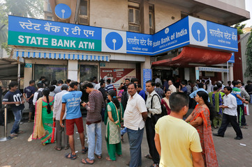 People queue as they wait for their turn to exchange or deposit their old high denomination banknotes outside a bank in a slum in Mumbai