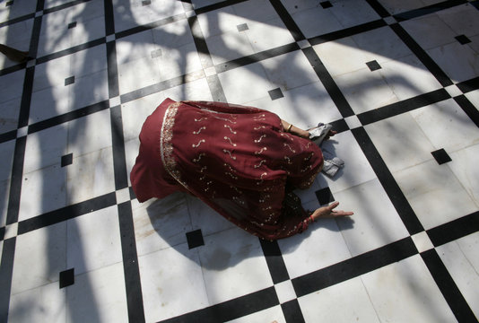 A Hindu woman prays while lying on the floor of a temple on the first day of the nine-day long Navratri festival in Jammu