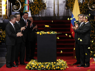 Colombia's President Juan Manuel Santos and his Mexican counterpart Enrique Pena Nieto applaud while standing next to an urn containing the ashes of late Colombian Nobel laureate Gabriel Garcia Marquez in Mexico City