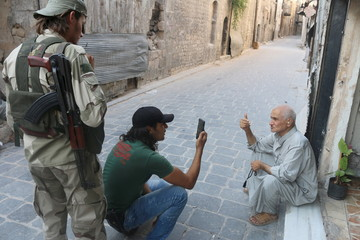 Free Syrian Army fighters take a picture of an old man using a mobile phone in Old Aleppo, Syria