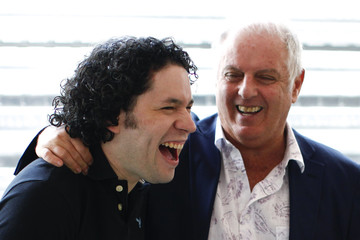 Orchestra conductors Barenboim and Dudamel laugh during a visit to the National System of Children and Youth Orchestras of Venezuela in Caracas