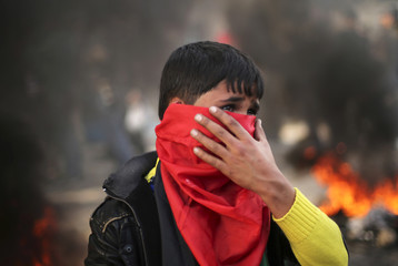 Palestinian boy stands near burning tyres during protest against decision by main U.N. aid agency to suspend payments to Palestinians for repairs to homes damaged in last summer's war, outside headquarters of UN Special Coordinator in Gaza