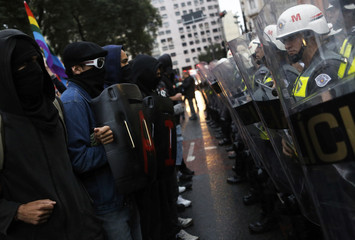 Demonstrators stand in front of a military police lineup during a protest against the 2014 World Cup in Sao Paulo
