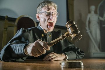 angry man a judge with a hammer in his hand in the court room shouts and cry
