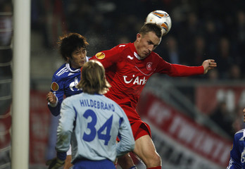 Schalke 04's Uchida and Twente Enschede's Cornelisse jump for the ball during their Europa League soccer match in Enschede