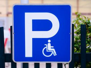 Blaues Verkehrsschild mit Rollstuhl kennzeichnet Behindertenparkplatz