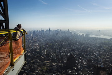 An iron worker leans on a safety fence to look at the New York skyline after watching a crane lift the final piece of the spire to the top of the One World Trade Center in New York