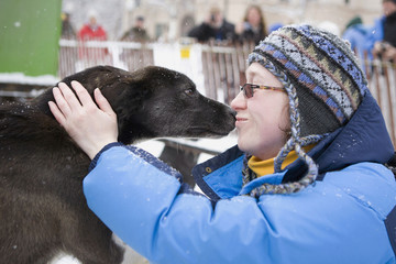 """Race fan Zoya Epshteyn of Seattle gets close-up with a dog, """"Aurora"""", from the team of Art Church, Jr during the ceremonial start of the 40th Iditarod Trail Sled Dog Race in downtown Anchorage"""