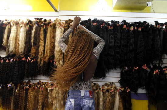 A seller displays hair extensions at a hair shop in a local market in Rio de Janeiro