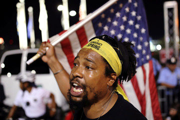 A man waves an American Flag as an activist group stages a sit in outside the Wells Fargo Center on the third day of the Democratic National Convention in Philadelphia