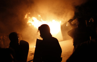 Bulgarian riot police walk in front of burning guardhouse outside a house during protest in the village of Katunitsa