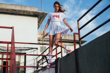 Fashion model jumps and poses like industry professional in front of camera, wind blows her skirt and hair