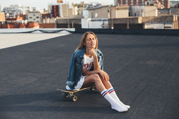 Young female in teenager millenial clothes rests on the rooftop on a sunny warm day in soft sunset light in beautiful shadow, wears hipster socks