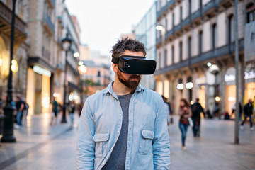 Trendy hipster bearded man lets the world pass by while he is deep into the virtual reality technology experience