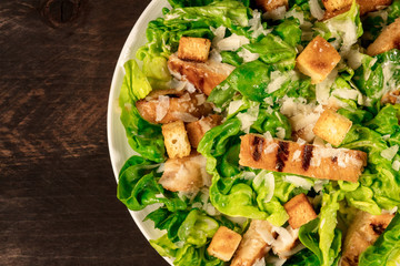 Closeup of plate of chicken Caesar salad on rustic texture