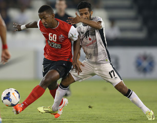 Basheer of UAE's Al-Ahli fights for the ball with AlYazidi of Qatar's Al-Sadd during their AFC Championship League match in Doha
