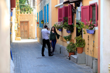 A man takes a picture of a woman posing in the old city of Tyre