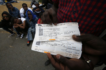 A Sudanese migrant displays his train ticket to travel to Paris on his way to Germany as he is blocked at the Franco-Italian border near Menton, France