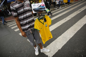 A street vendor holding a Brazil national soccer team jersey waits for customers in Sao Paulo