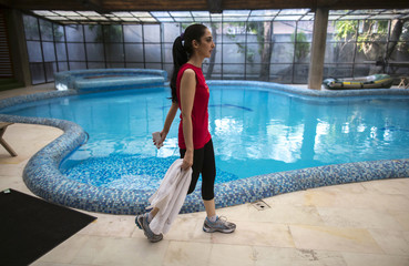 Educationalist and model Fatima walks past the swimming pool after working out in her gym at her house in Lahore