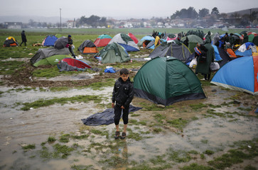 A migrant walks in a mud at a makeshift camp on the Greek-Macedonian border, near the village of Idomeni
