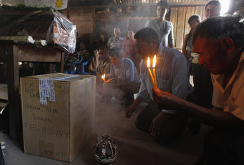 People pray next to box containing the skeleton of Martina Rojas, who disappeared during internal armed conflict in Rabinal
