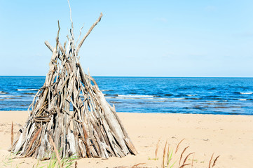 Wigwam Made from wooden branches on the sand of baltic sea beach