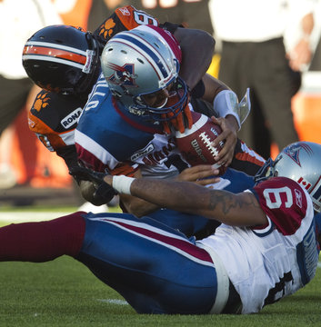 Montreal Alouettes quarterback Cavillo is sacked by BC Lions' Hunt during CFL play in Vancouver
