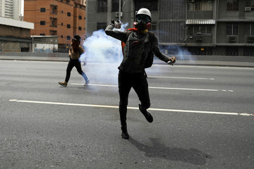 A demonstrator throws a tear gas canister back during clashes with riot security forces during a rally called by health care workers and opposition activists against Venezuela's President Nicolas Maduro in Caracas