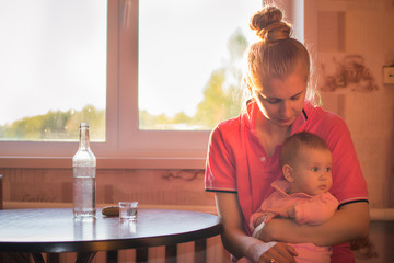 A young mother and a beautiful baby are sitting at the kitchen table on which stands a bottle of alcohol, a glass and a pickled cucumber. Social problem: female alcoholism