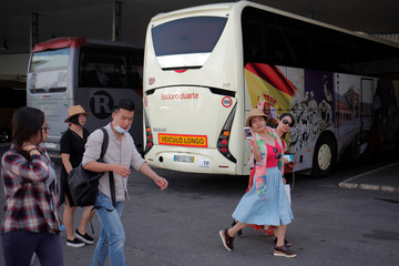 Asian tourists walk at the bus station after a tour in Ronda