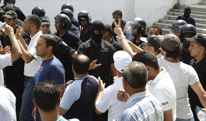 Protesters demonstrate against the Tunisian interim government in front of riot police at Kasbah square in Tunis