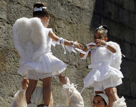 """Five-year-old girls dance on the shoulders of women during the """"Coca"""" celebration in Redondela in rural northeastern Spain"""