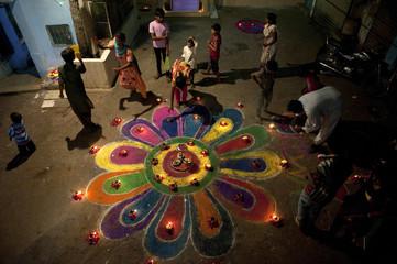 "Members of the Pakistani Hindu community stand around a ""rangoli"" during Diwali in Karachi"