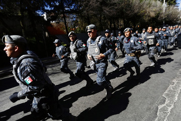 Police officers run near the site of an explosion at a maternity hospital in Mexico City