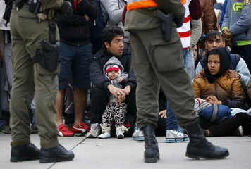 Members of the Austrian army guard a group of migrants waiting for transport at the Austrian border in Spielfeld