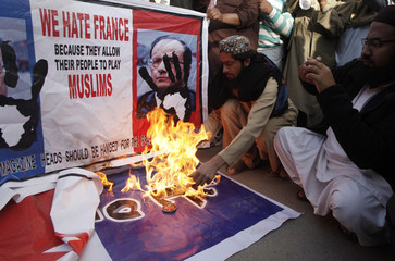 A man burns posters during a protest against Charlie Hebdo, which featured a cartoon of the Prophet Mohammad as the cover of its first edition since an attack by Islamist gunmen, in Quetta