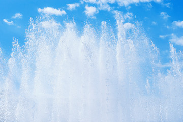 Fountain splashing jets against blue cloudy sky