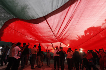 People walk under a massive national flag of Bangladesh as they attend a mass demonstration at Shahbagh intersection in Dhaka