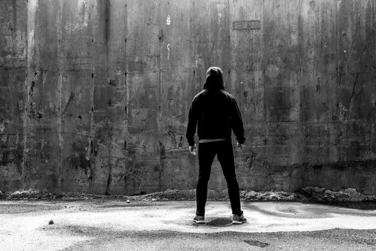 Man In A Black Hoodie and Jeans Facing A Concrete Wall
