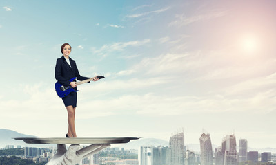 Attractive businesswoman on metal tray playing electric guitar against cityscape background