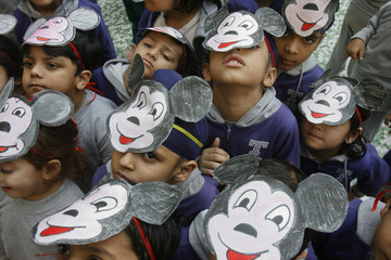 School student pose for pictures during celebrations for the 83rd birthday of cartoon character Mickey Mouse at a school in the northern Indian city of Chandigarh