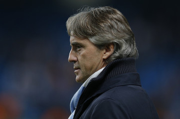 Manchester City's manager Roberto Mancini watches the warmup before the Champions League Group D soccer match against Real Madrid at The Etihad Stadium in Manchester