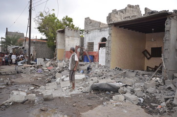 A man stands on the wreckage of a house destroyed by a Saudi-led air strike in Yemen's Red Sea port city of Houdieda