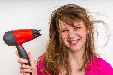 Fashion girl with hair dryer dries her hair