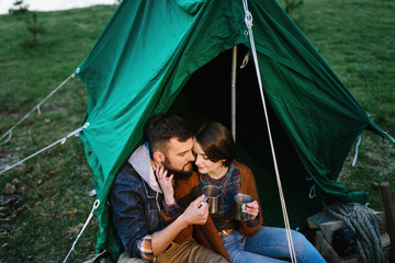 Man and woman in nature in a tent drink hot tea