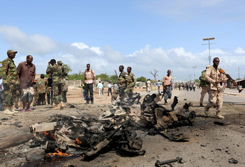 Somali government forces assess the scene of a suicide car explosion in Hodan district in the capital Mogadishu